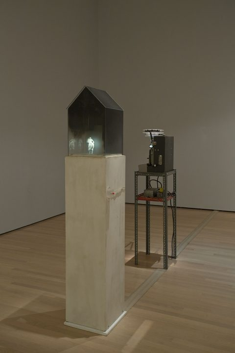 Home, 1986, Wyn Geleynse, Verre, noir de fumée, bois peint, projecteur, support de métal et film 16 mm noir et blanc, projection en boucle, 1 min. 10 sec. muet.