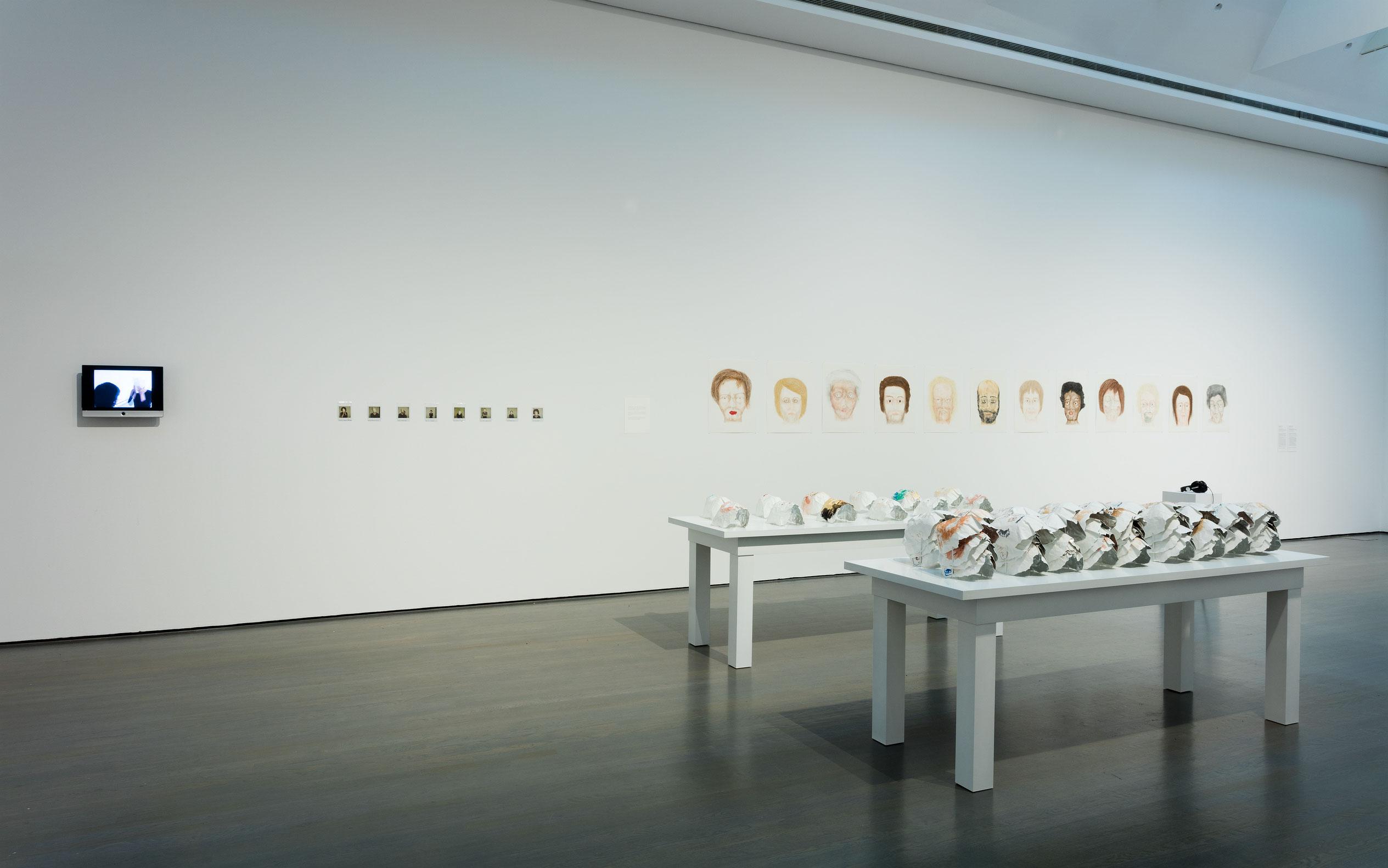 Tous ces visages, 2007-2008, Raphaëlle de Groot, Dessins (crayon de couleur, crayon-feutre et pastel sec sur papier), masques (crayon de couleur, crayon-feutre, aquarelle, papier, ruban aluminium), photographies Polaroid, vidéogramme, son, texte et tables de présentation.